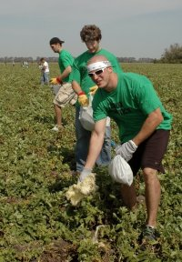 UND hockey players (front to back) Kyle Radke, Taylor Chorney and Joe Finley help clear a field of debris.