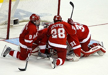 Dejected Miami players Tommy Wingels, Bill Loupee and Connor Knapp console goalie Cody Reichard (photo: Jim Rosvold).