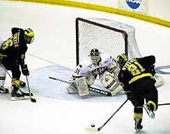 Michigan's Erik Nystrom comes in on DU goalie Wade Dubielewicz in the Pioneers' season-ending loss on Saturday. (photo by Christopher Brian Dudek)