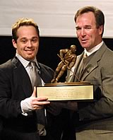 Rocky Reeves accepts the 2002 Hockey Humanitarian Award from [nl]Notre Dame coach Dave Poulin. (Photos by Pedro Cancel)