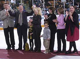 Bob Olson (second from left) acknowledges the crowd during a pre-game ceremony in his honor. Standing with him are MTU coach Mike Sertich, daughters Ramona, Kristina, Julie and Perian, and two granddaughters.