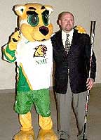 New NMU coach Walt Kyle poses at the news conference with the team mascot.