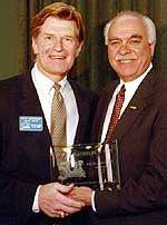 Magnuson (l.), in 2002, accepts his award from WCHA commissioner Bruce McLeod for being named to the conference's all-time team.