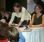 Chanda Gunn and Angela Ruggiero sign autographs for young fans.