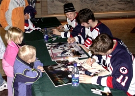 The trio signs autographs at UND's Ralph Engelstad Arena in Grand Forks.