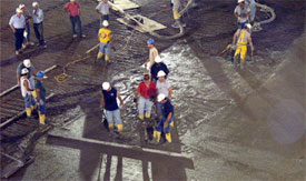 Workers pour the concrete onto the new Agganis Arena floor.