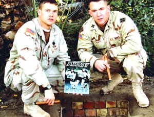 Brody Howatt (r.) and John [nl]Williams, also a former Army icer, pose over Saddam's spider hole with the Black Knights' media guide. (Courtesy Army Sports Information)