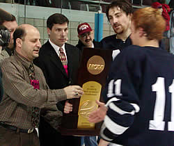 Middlebury's John Dawson and Kevin Cooper (11) accept the national championship trophy from Vince Eruzione (left) and Dan Stauber. (photo by Ed Trefzger)