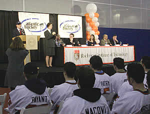 Members of the RIT hockey team look on as RIT president Al Simone speaks.