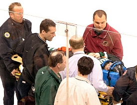 Emergency personnel take UND's Robbie Bina off the ice at the WCHA Final Five.