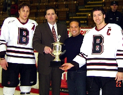 Assistant Captain Gerry Burke '05, Head Coach Roger Grillo, Providence Mayor David Cicilline (Brown Class of '83), and Captain Les Haggett '05 accepting the Mayor's Cup after last year's 5-1 Brown win (photo: Brown sports information).