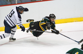 St. Norbert captain Connor Hughes dives for a loose puck past Middlebury's Eric LaFreniere.