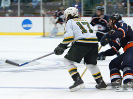 Connor Hughes chases the loose puck during overtime. Hughes tallied the winning goal for St. Norbert. (photo: Angelo Lisuzzo)