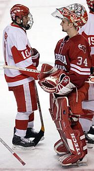 Chris Higgins (l.) shakes hands with UNO netminder Jerad Kaufmann in the wake of Higgins' hat trick and BU's 9-2 win (photo: Melissa Wade).