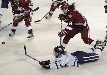 UNH's Martine Garland (2) gets a shot off from ice level as she's tripped up by Harvard's Laura Brady in the third period. (Photo: Josh Gibney)