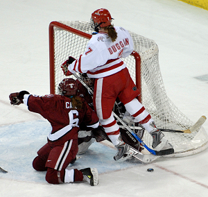 Cahow (front) takes a hit from Wisconsin's Meghan Duggan during action in the 2007 NCAA tournament (photo: John E. Van Barriger, words-photos.com).