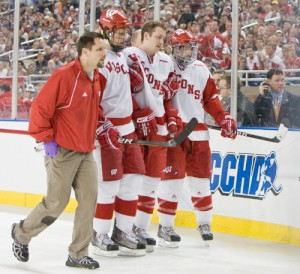 Wisconsin's Derek Stepan is helped off the ice by Andy Hrodey, Blake Geoffrion and Podge Turnbull after crashing into the boards (photo: Melissa Wade).