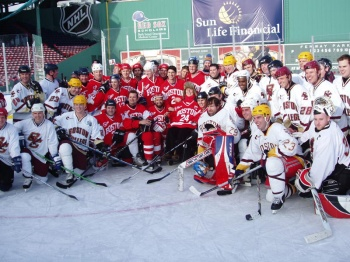 Old rivalries took a back seat to good times at Fenway Park when alumni from Boston University and Boston College skated. Afterward, the teams pose for photos with Travis Roy (photo: Brian Sullivan).