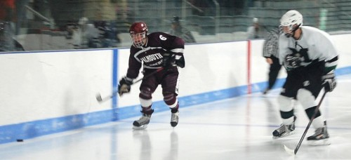 Brennan Quackenbush (right) lines up an opposing forward on the boards.