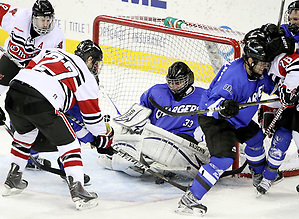 Alabama-Huntsville goalie Clarke Saunders traps the puck under his pads as UNO's Matt Ambroz (No. 27) and Rich Purslow (No. 9) close in. Saunders finished with 58 saves. Alabama-Huntsville beat UNO 2-1 in overtime Saturday night at Qwest Center Omaha. (Photo by Michelle Bishop) (Michelle Bishop)