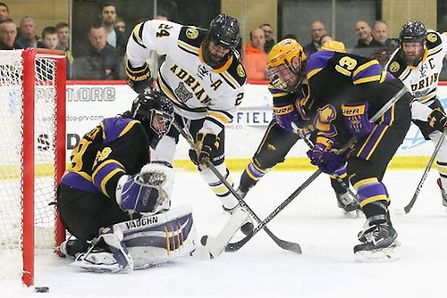 Wisconsin-Stevens Point goaltender Max Milosek makes a save with Adrian's Daniel Lisi and the Pointer's Nathan Harris in front. (Mike Dickie Photography)